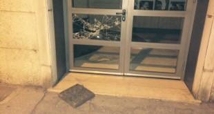 La porta di ingresso, a vetri, del cinema Roma ed il tombino usato per spaccarla
